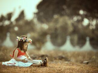 Petite fille qui lit un livre dans la nature